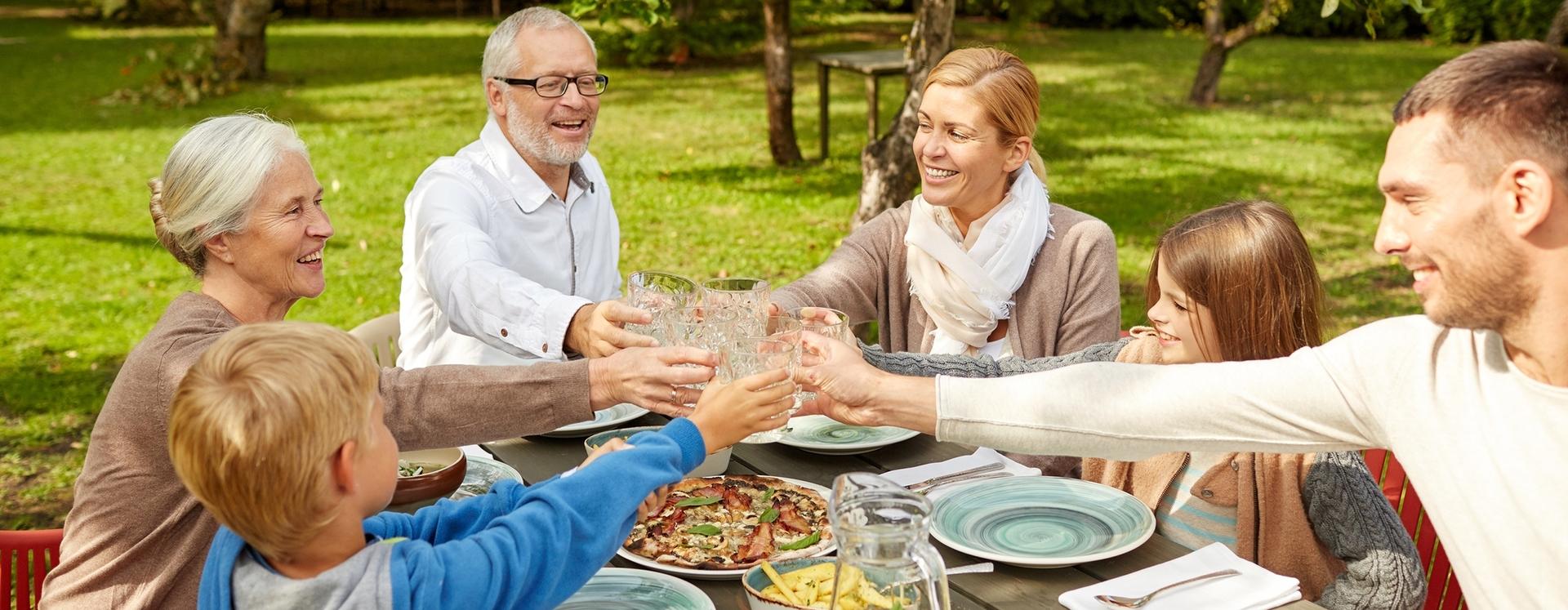 Großfamilie beim Essen im Bauerngarten