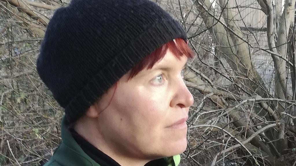 Frau mit Mütze auf dem Kopf schaut zur Seite.