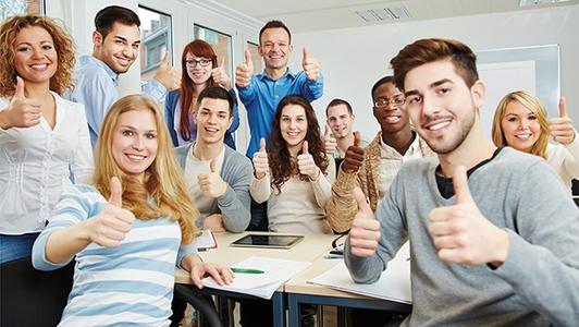 Auszubildende in der Klasse mit Daumen hoch