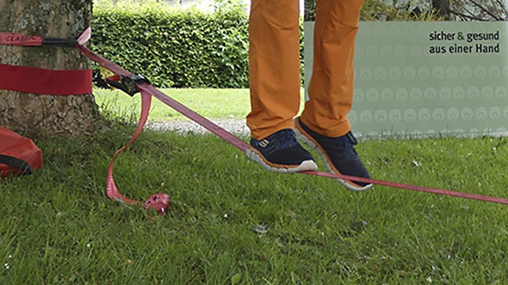 Detailfoto zeigt die Beine von einer Person, die auf einer Slackline trainiert