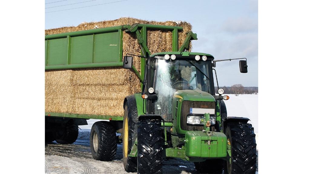Traktor mit Anhänger, auf dem Strohballen geladen sind