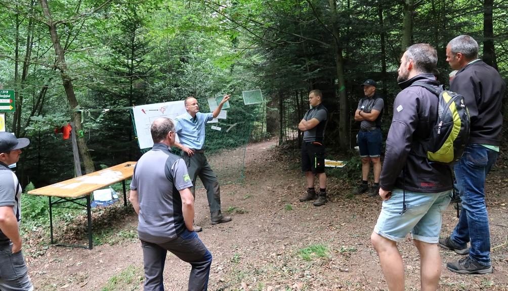 Bild: Mann erklärt mehreren Personen die Station Arbeitsauftrag im Wald